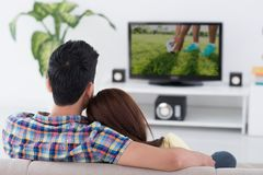 Game on tv. Couple watching soccer game on tv, view from the back Royalty Free Stock Photography