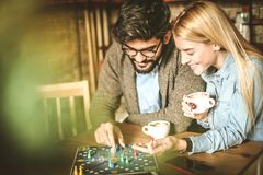 Game. Two friends playing game. Young couple playing leisure games together. Friends at cafe together Royalty Free Stock Image