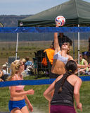 Game of volleyball with a woman spiking the ball. Royalty Free Stock Photos