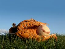 Game Well Played!. Brown new leather glove & baseball in field of green on a clear day Royalty Free Stock Photo