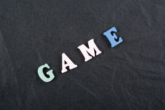 GAME word on black board background composed from colorful abc alphabet block wooden letters, copy space for ad text. Learning english concept Royalty Free Stock Photography