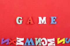 GAME word on red background composed from colorful abc alphabet block wooden letters, copy space for ad text. Learning Stock Image
