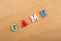 GAME word on wooden background composed from colorful abc alphabet block wooden letters, copy space for ad text. Learning english concept royalty free stock photos