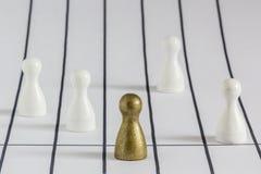 Gamefigurine del oro delante del blanco unos, señalando ganar y la dirección imagen de archivo libre de regalías