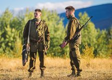 Gamekeepers walk mountains background. Gamekeepers sunny fall day. Gamekeeper occupation concept. Hunting with partner. Provide greater safety fun and rewarding stock image
