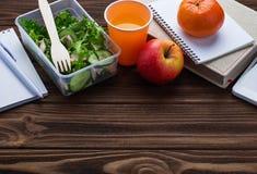 Gamelle avec de la salade, la pomme, la mandarine et le jus Images libres de droits