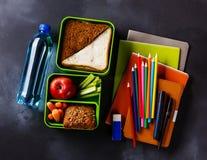 Gamelle avec les sandwichs, la bouteille de bouteille de l'eau et les fournitures scolaires Photo stock