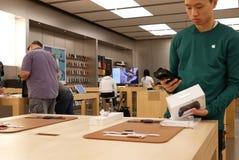 Gamepad de la exploración del trabajador para el cliente dentro de Apple Store Fotos de archivo libres de regalías