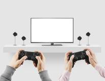 Gamepad della tenuta dell'uomo in mani davanti a derisione in bianco dello schermo della TV sul pl Fotografie Stock