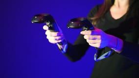 Gamepad en gros plan de VR, contrôleur à distance, jeu vidéo interactif de jeu de femme Deux contrôleurs de réalité virtuelle sur banque de vidéos