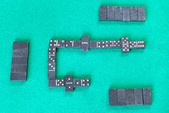 Gameplay of dominoes board game with black tiles. Top view of gameplay of dominoes board game with black tiles on green baize table stock photo