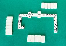Gameplay of dominoes board game with white tiles. Top view of gameplay of dominoes board game with white tiles on green baize table stock photo