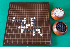 Gameplay of Go game and playing stones in bowls. Top view of gameplay of Go game and playing stones in bowls and wooden board on green table royalty free stock photos