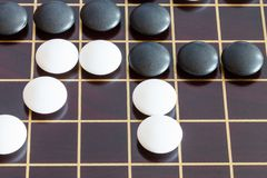 Gameplay of Go game on wooden board close up. Gameplay of Go game on brown wooden board close up stock images