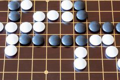 Gameplay of Go game on wooden board. Top view of gameplay of Go game on wooden board royalty free stock images