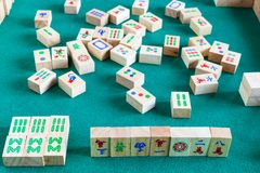 Gameplay of mahjong board game. Gameplay of mahjong game, tile-based chinese strategy board game on green baize table stock photography