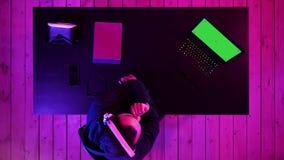 Gamer που φορά το ρεύμα προσοχής κασκών ενός παιχνιδιού Πράσινη επίδειξη προτύπων οθόνης απόθεμα βίντεο