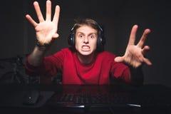 Gamer играет игры дома на компьютере Молодой человек играет видеоигру и сердится на отказе стоковое фото rf