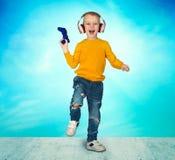 Gamer мальчика в наушниках с кнюппелем играя компютерную игру Изолировано на голубой предпосылке стоковые изображения rf
