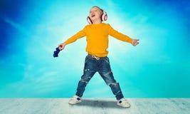 Gamer мальчика в наушниках с кнюппелем играя компютерную игру Изолировано на голубой предпосылке стоковое изображение