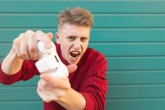 Gamer с gamepad в его руках играя игры консоли, смотря в камеру на покрашенной предпосылке стоковые фото