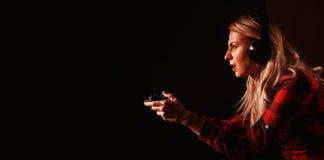 Gamer девушки в наушниках и при кнюппель восторженно играя на консоли стоковые фотографии rf