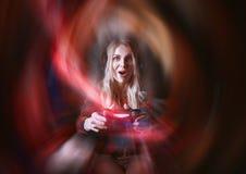 Gamer девушки в наушниках и с кнюппелем в ее руках играя игры сети подготавливая участвовать в международном competit стоковое изображение