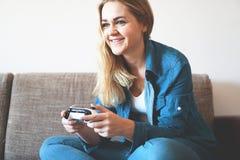 Gamer девушки играет с беспроводным gamepad пока смотрящ экран, видеоигры стоковое фото