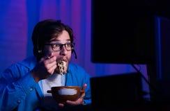 Gamer есть лапши, играя онлайн видеоигры стоковое фото rf
