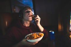 Gamer ест обломоки Фаст-фуд на почти стоковые изображения