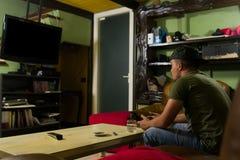 Gamer играет игры в его грязной комнате стоковое изображение rf