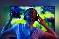 Gamer или девушка ленты дома в темной комнате с gamepad играя с друзьями на сетях в видеоиграх Молодой человек стоковое изображение rf
