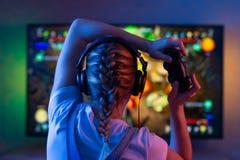 Gamer или девушка ленты дома в темной комнате с gamepad играя с друзьями на сетях в видеоиграх Молодой человек стоковые фотографии rf