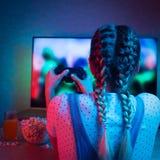 Gamer или девушка ленты дома в темной комнате с gamepad, играя с друзьями онлайн в видеоиграх с попкорном и мульти- стоковое изображение rf