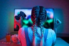 Gamer или девушка ленты дома в темной комнате с gamepad, играя с друзьями онлайн в видеоиграх с попкорном и стоковая фотография rf