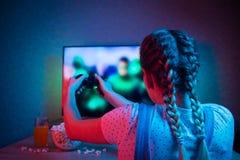 Gamer или девушка ленты дома в темной комнате с gamepad, играя с друзьями онлайн в видеоиграх с попкорном и мульти- стоковые изображения rf