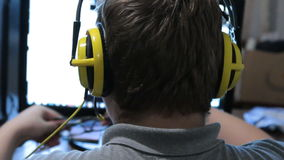 Gamer from back in yellow headphones sits in front of a monitor with video game in room. stock footage