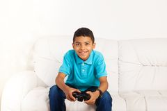 Gamer boy. Happy smiling black boy playing video games holding game controller sitting on the coach in living room Royalty Free Stock Images