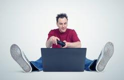 Gamer che si siede sul pavimento che gioca sul computer portatile Immagine Stock Libera da Diritti