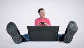 Gamer che si siede sul pavimento che gioca sul computer portatile Fotografia Stock