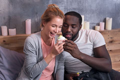 Gamer couple eating cupcakes in bedroom Royalty Free Stock Image