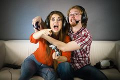 Gamer couple playing games. Couple enjoying leisure time by playing video games together, men and women being emotional by game Stock Images