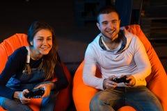 Gamer de deux jeunes s'asseyant sur des poufs et jouant le togethe de jeux vidéo Photographie stock libre de droits