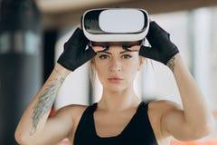 Gamer die vergrote werkelijkheidsglazen dragen die zich in het in dozen doen houding het spelen het spelmobiele toepassing van de stock foto's