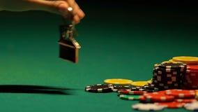 Gamer disperato della mazza che mette le chiavi vicino ai chip del casinò, ultima opportunità della casa di vincere archivi video