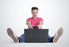 Gamer divertente dell'uomo che si siede sul pavimento che gioca sul computer portatile Immagini Stock Libere da Diritti
