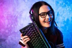 Gamer dziewczyna bawi? si? z komputerem w domu M?ody ?e?ski pozowa? z komputerow? klawiatur? obraz stock