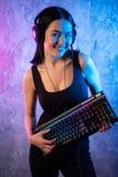 Gamer dziewczyna bawi? si? z komputerem w domu M?ody ?e?ski pozowa? z komputerow? klawiatur? obrazy stock