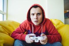 Gamer emozionale che si siede sullo strato e che gioca i videogiochi con un gamepad Vista messa a fuoco della macchina fotografic Fotografie Stock