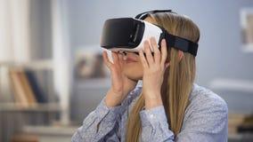 Gamer femminile emozionante che guarda intorno in vetri di realtà virtuale, innovazione video d archivio